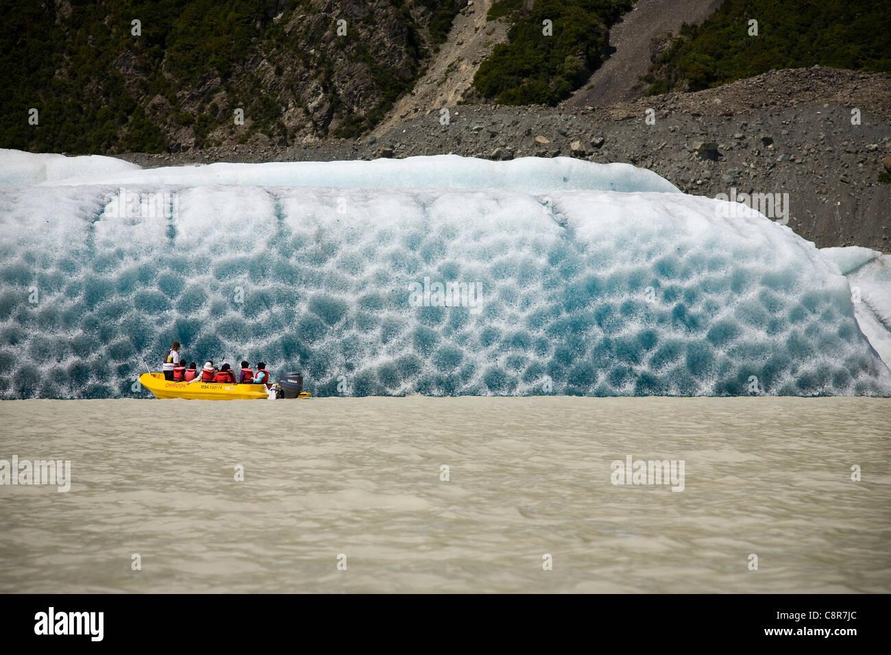 Tourists get close to an iceberg in the Tasman Glacier Terminal Lake, New Zealand Stock Photo