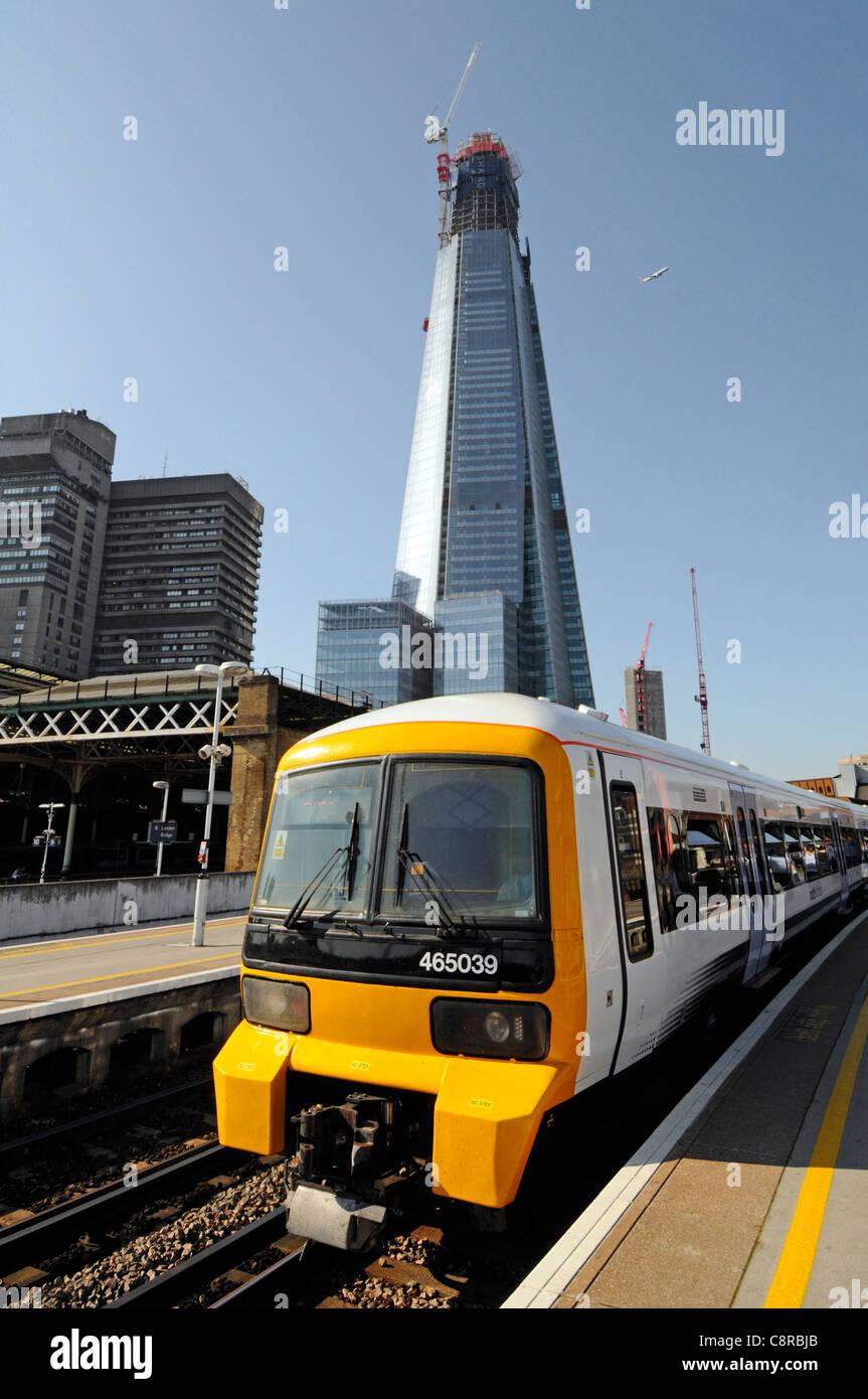 Work in progress at Shard landmark skyscraper building site under construction beyond London Bridge train station - Stock Image