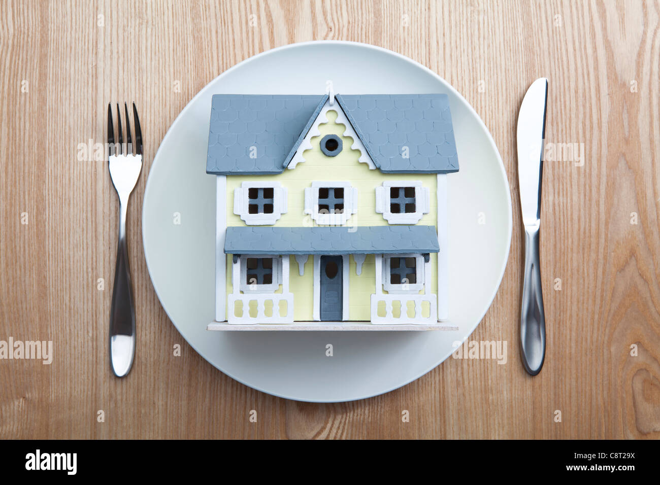 Top view of architectural model placed in plate with fork and knife on table - Stock Image