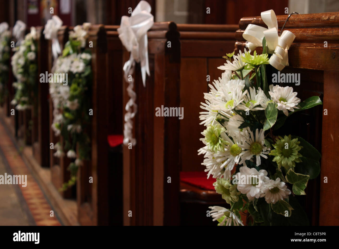 Church pews with wedding floral arrangements of flowers in green and church pews with wedding floral arrangements of flowers in green and white at the end of each pew junglespirit Image collections