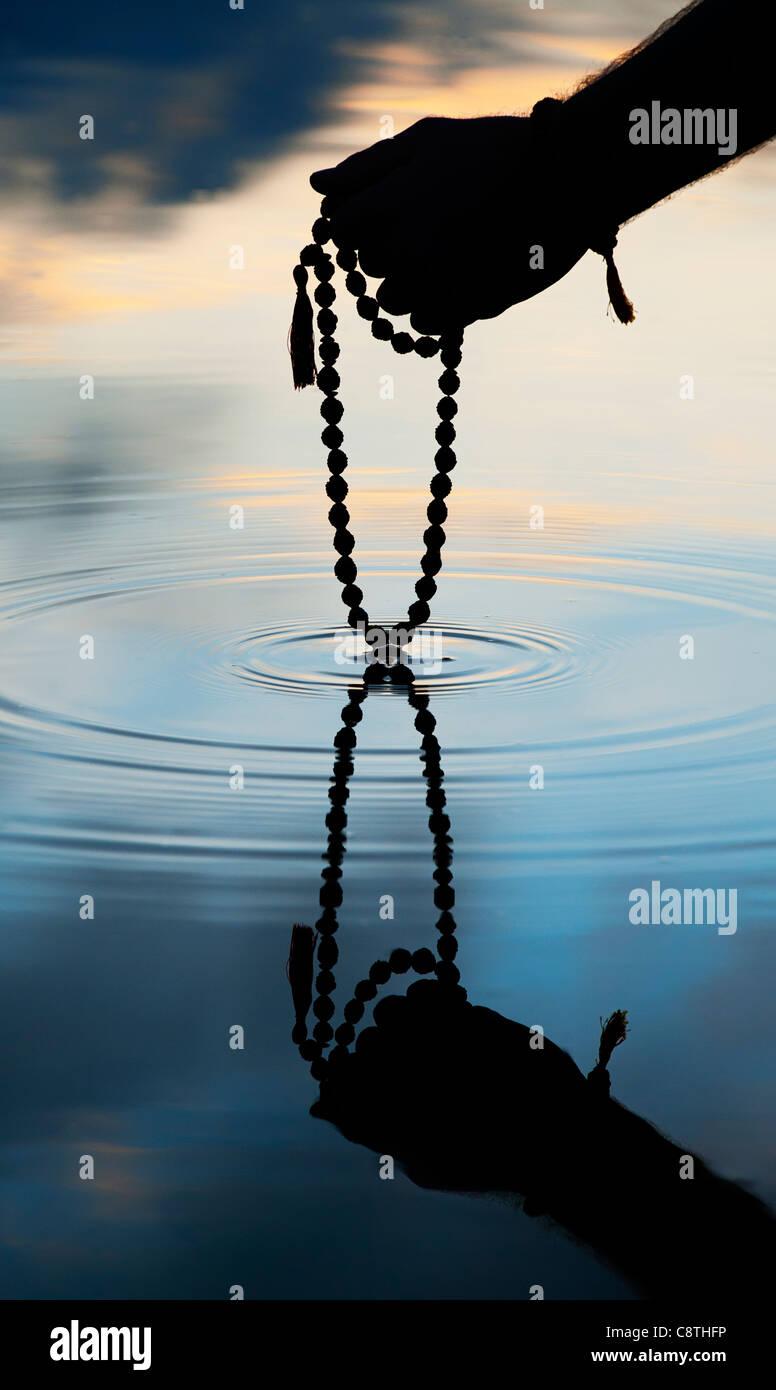 Hand holding Indian Rudraksha / Japa Mala prayer beads over rippling water . Silhouette - Stock Image