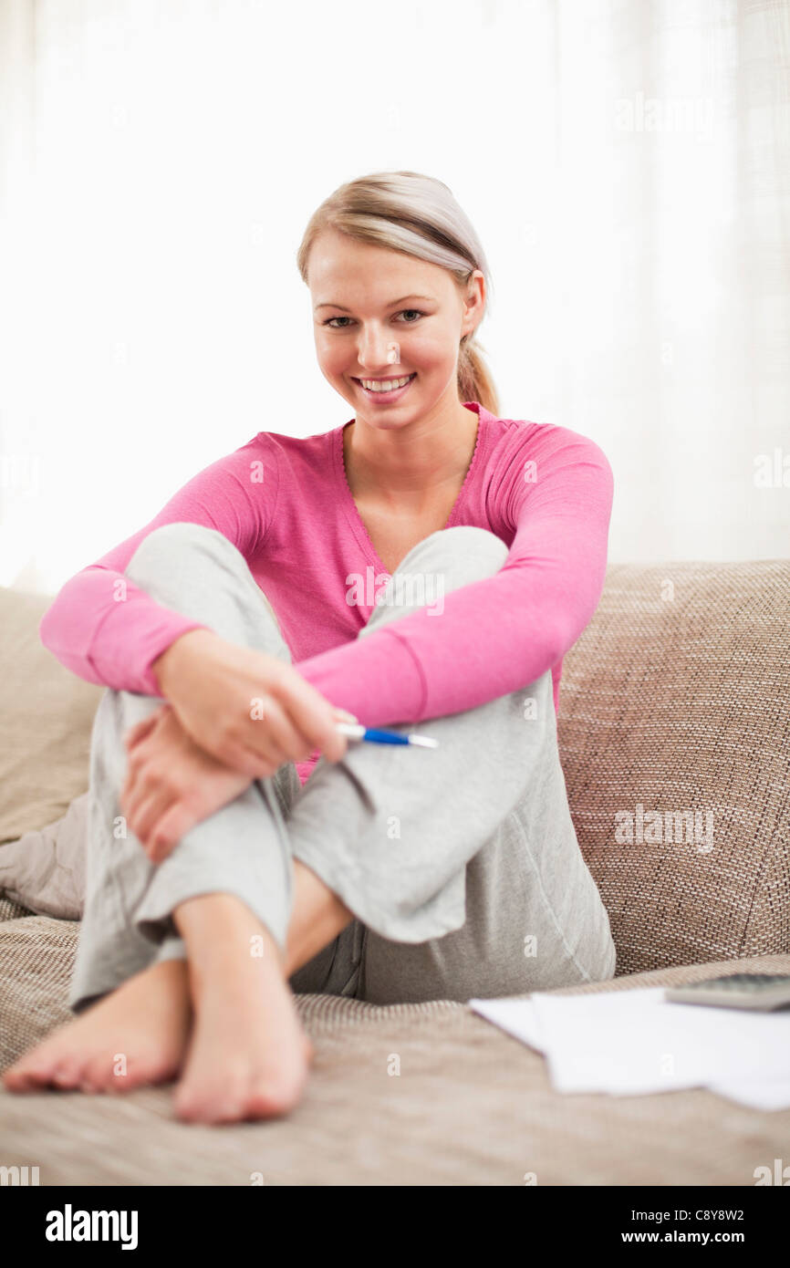 portrait of young woman at home working on personal finance - Stock Image