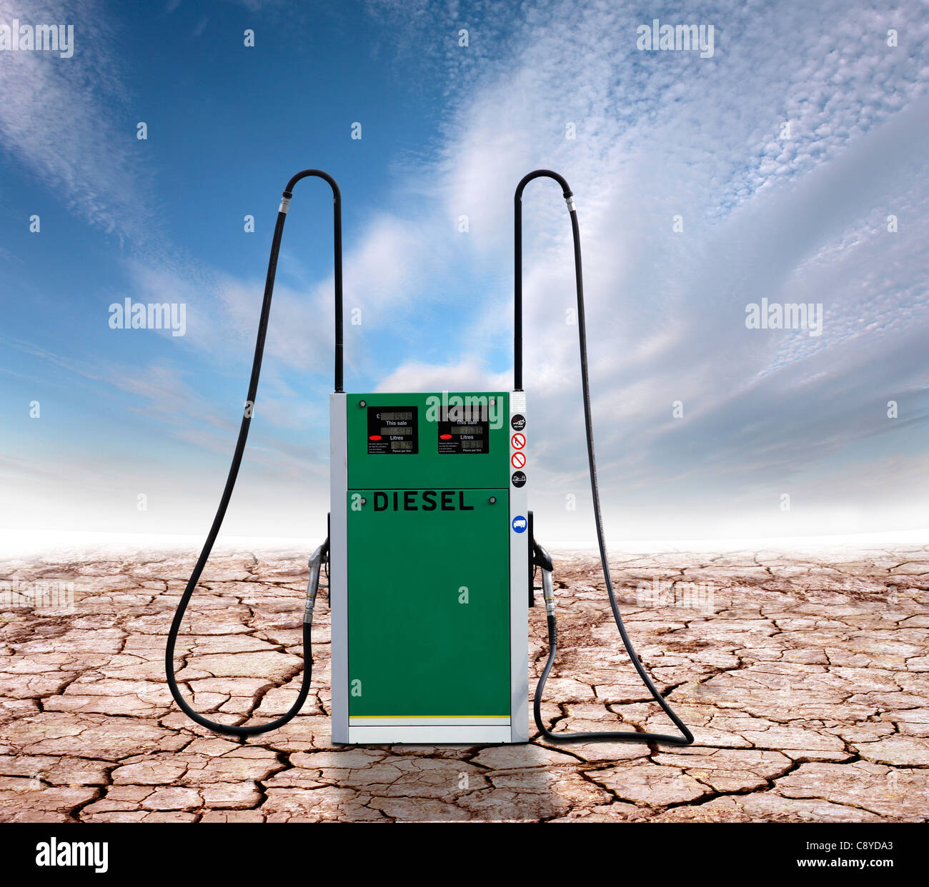 Diesel pump on a cracked earth background, representing climate change due to use of fossil fuels. - Stock Image