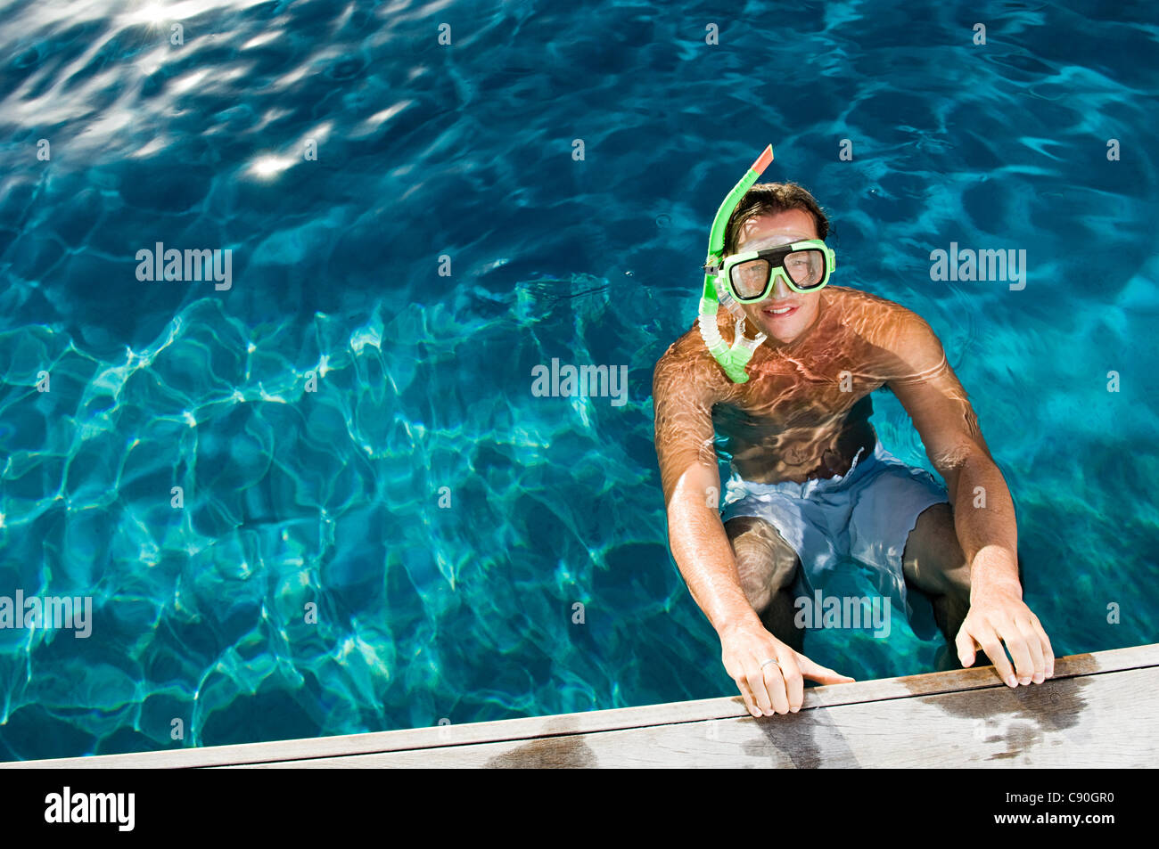 Young man wearing snorkel at poolside, high angle - Stock Image