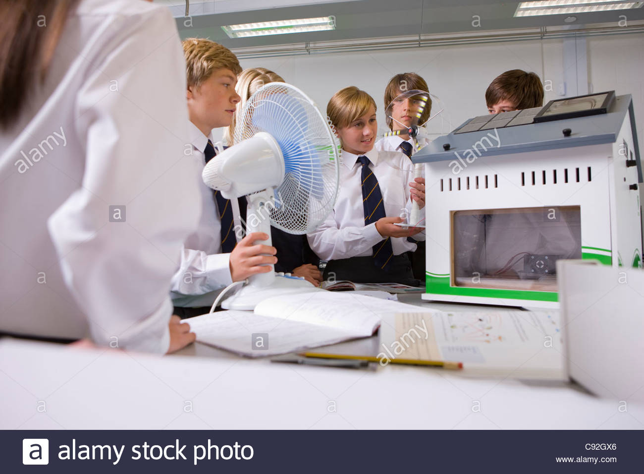 Students experimenting with model wind turbine in science class - Stock Image