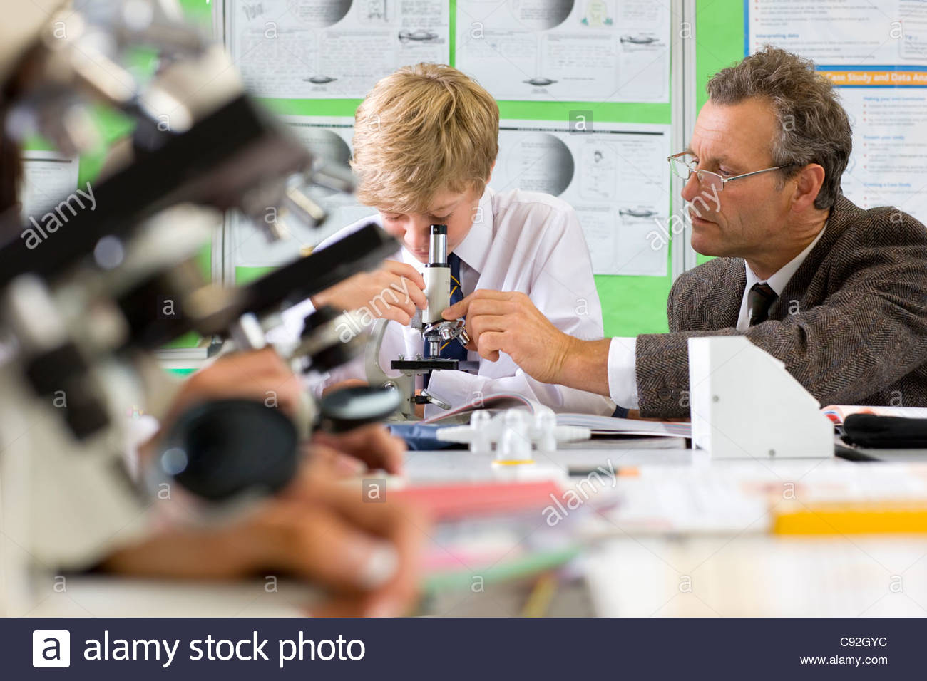 Student and teacher with microscope in science class - Stock Image