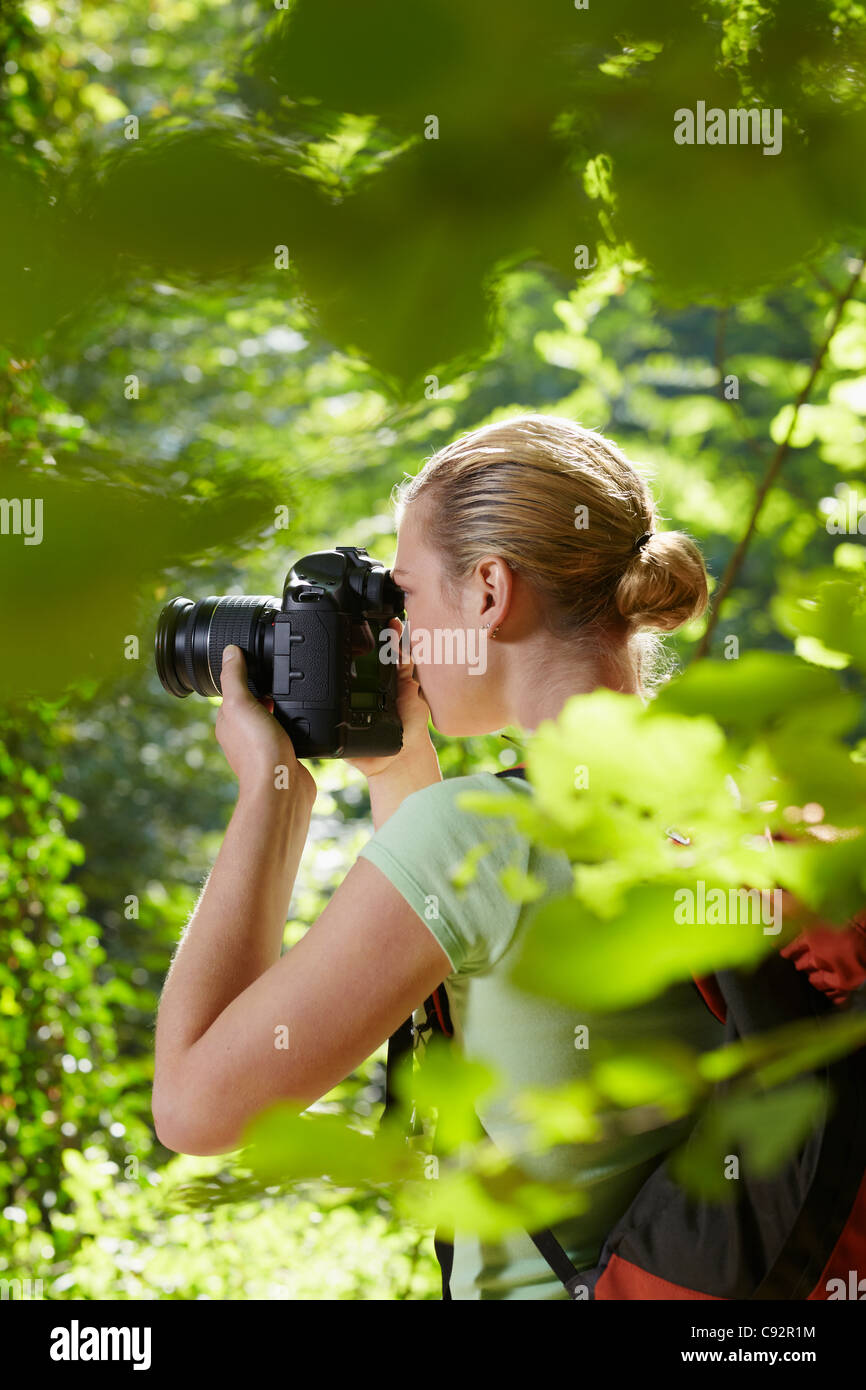 young woman trekking among trees and taking pictures with dslr camera. Vertical shape, side view, waist up, copy - Stock Image