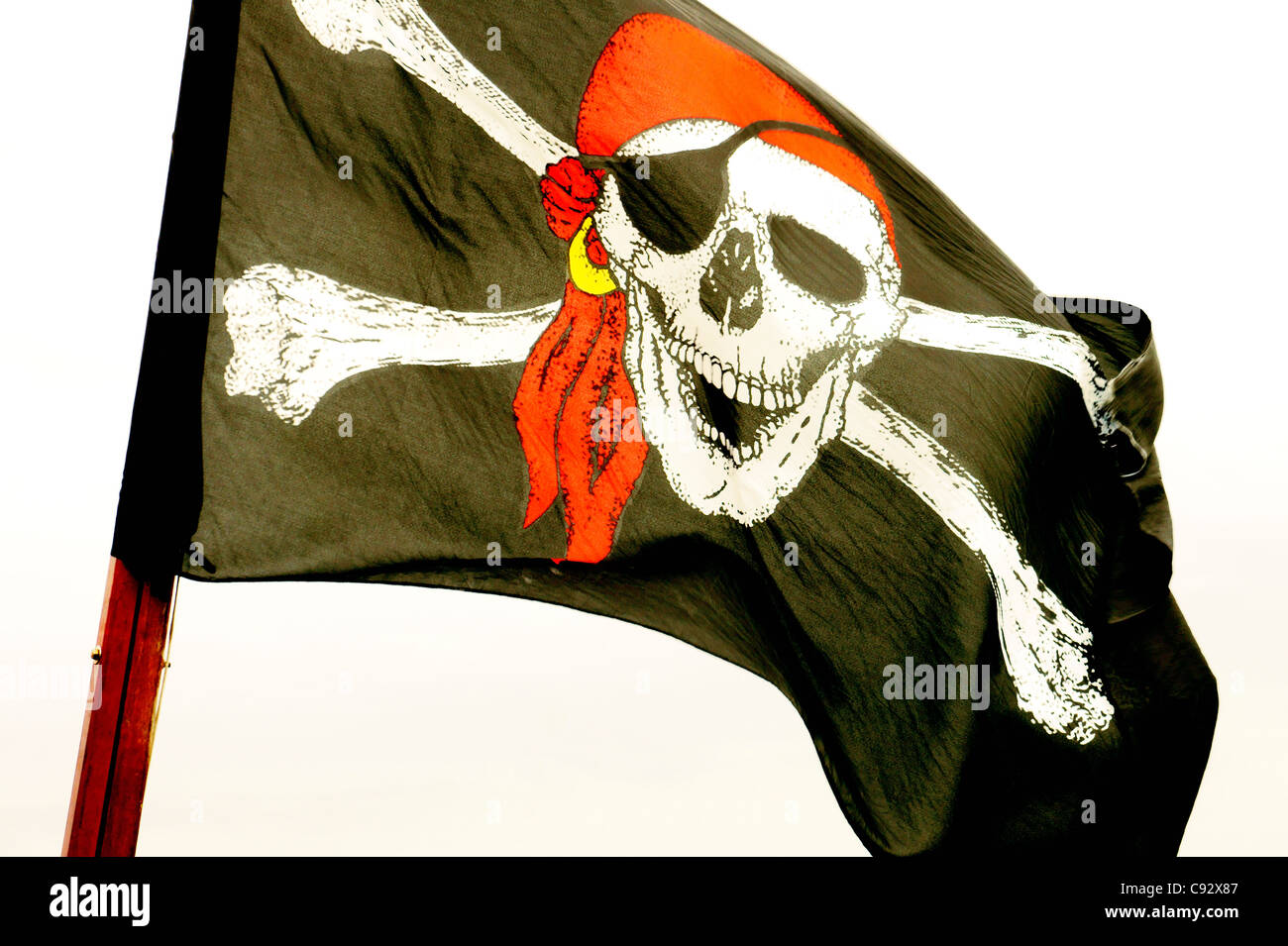 The Jolly Roger skull and cross bones pirate flag - Stock Image