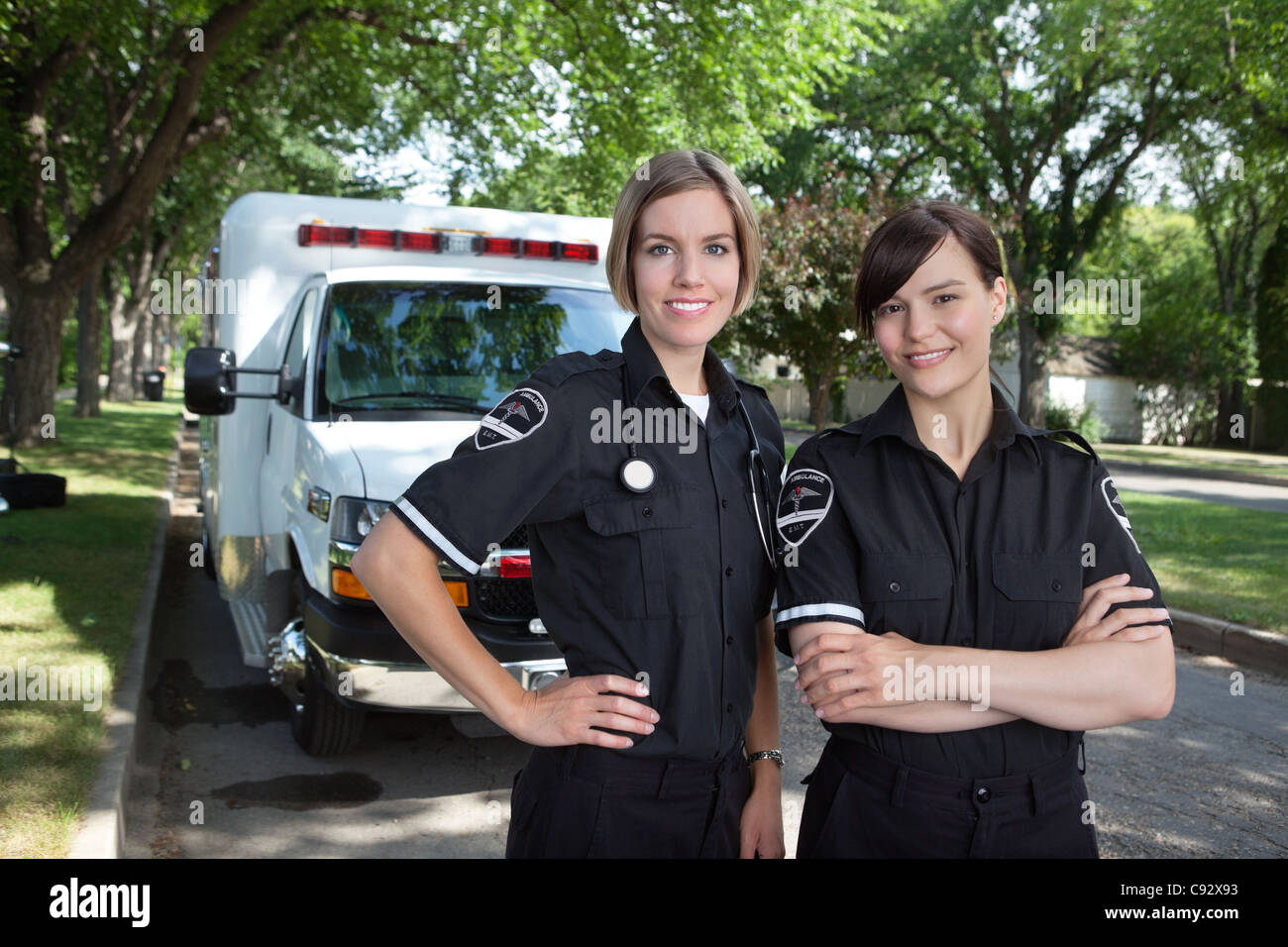 Female paramedica team portrat in front of ambulance - Stock Image