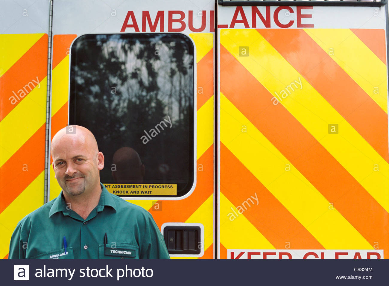 Portrait of smiling paramedic in front of ambulance - Stock Image