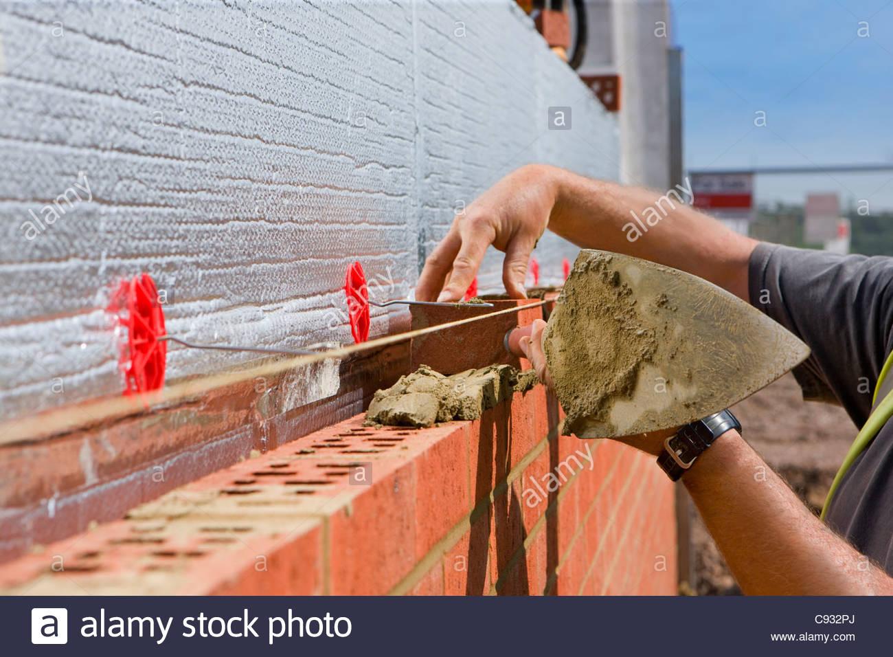 Bricklayer laying brick wall - Stock Image