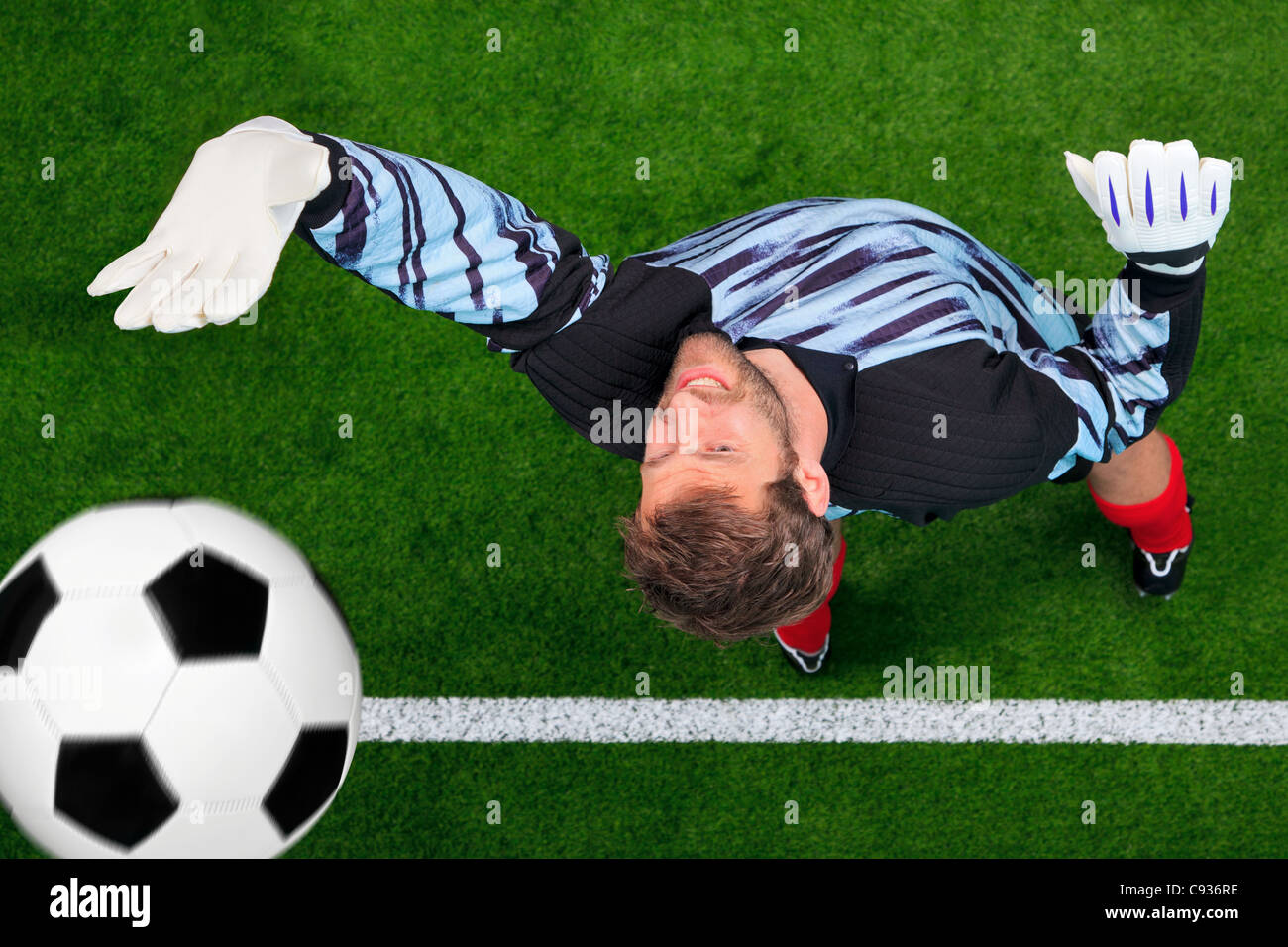 Overhead photo of a football goalkeeper missing saving the ball as it crosses over the line. - Stock Image