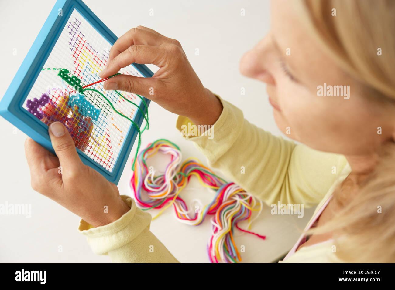 Mid age woman doing cross stitch - Stock Image
