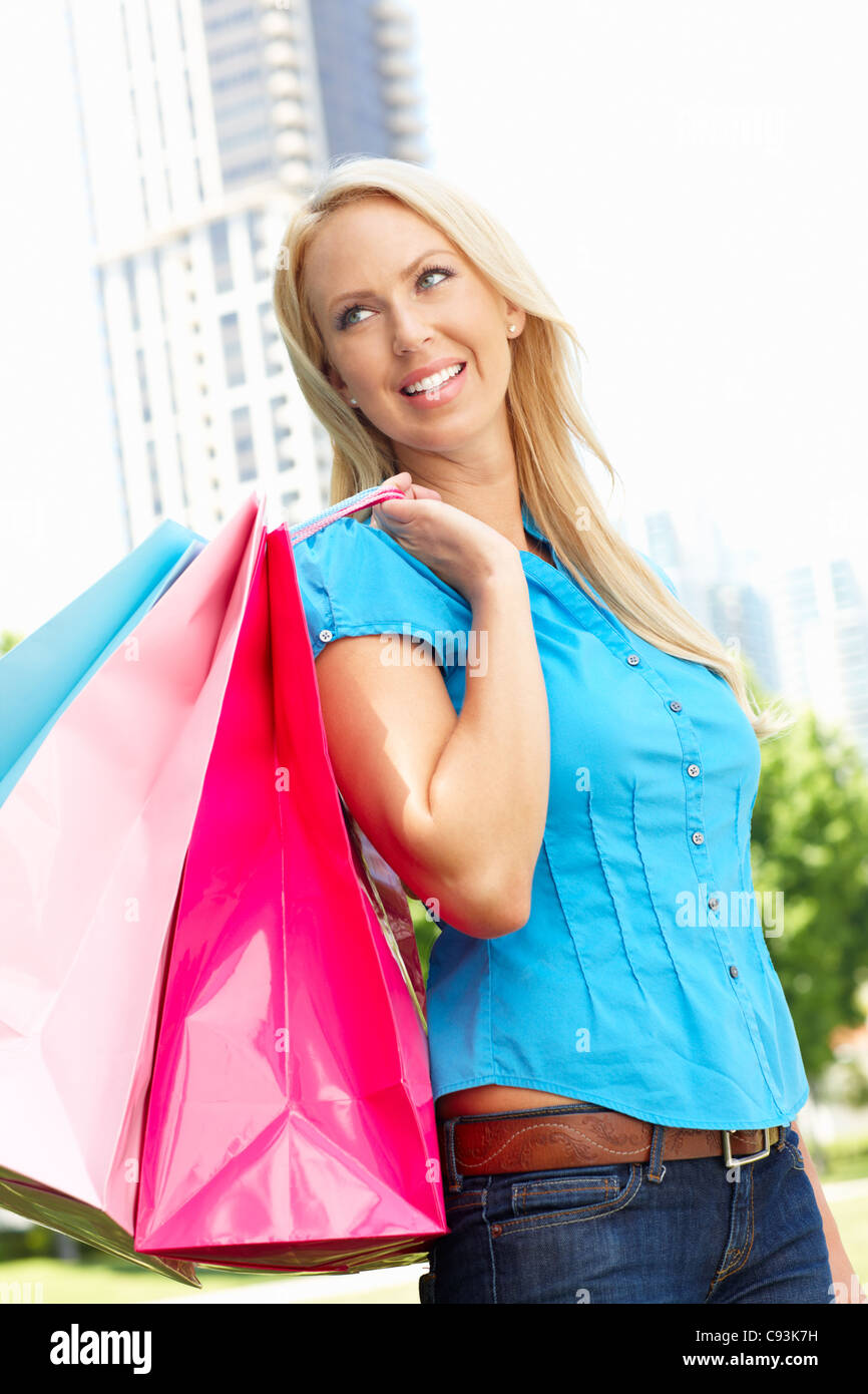 Woman carrying shopping bags in city park - Stock Image