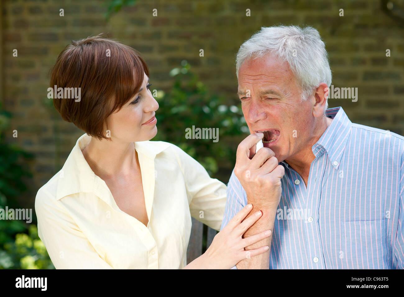 Man using angina spray. - Stock Image