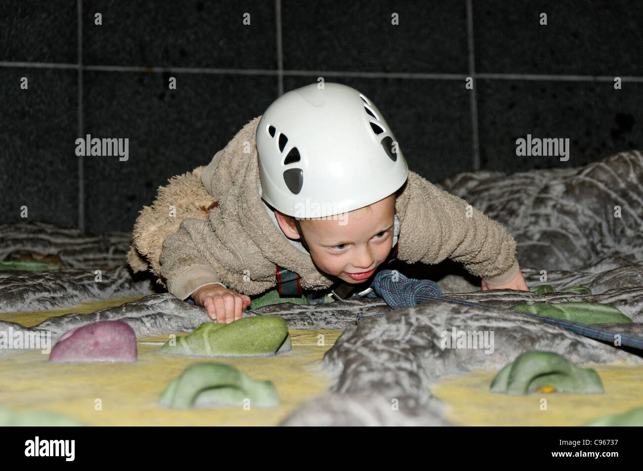 A young boy on an indoor climbing wall - Stock Image