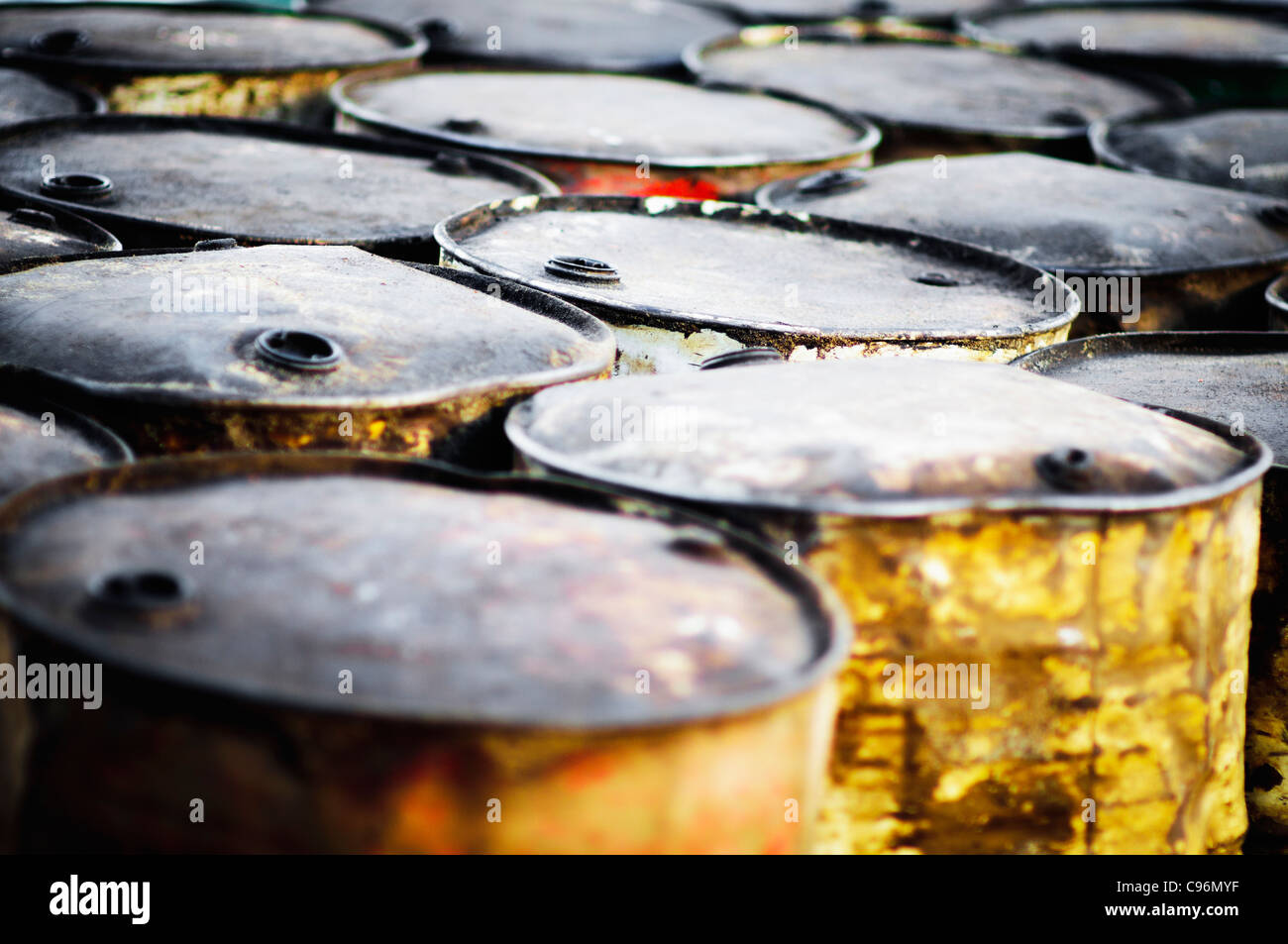 Old rusty oil barrels on the beach of Gili Meno in Indonesia - Stock Image