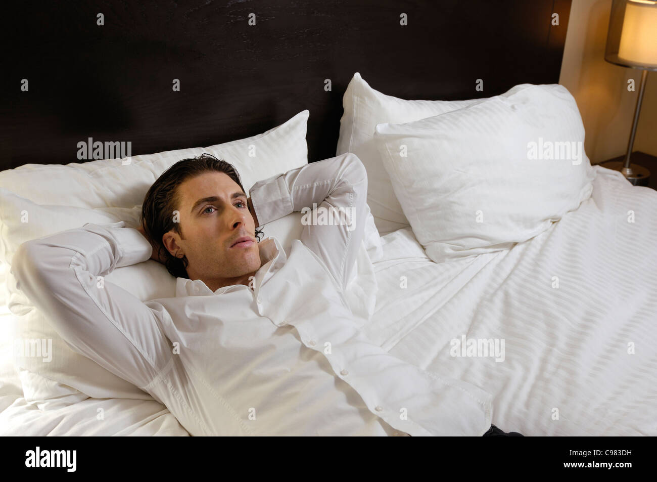 Young man lying alone in bed with thoughtful expression - Stock Image