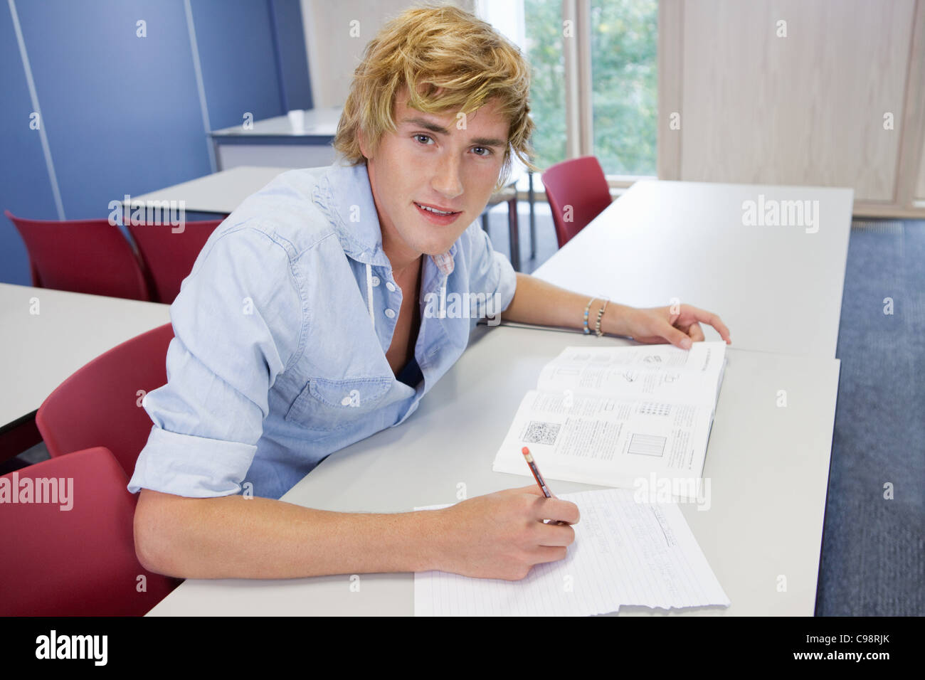 University student writing on exam paper class - Stock Image