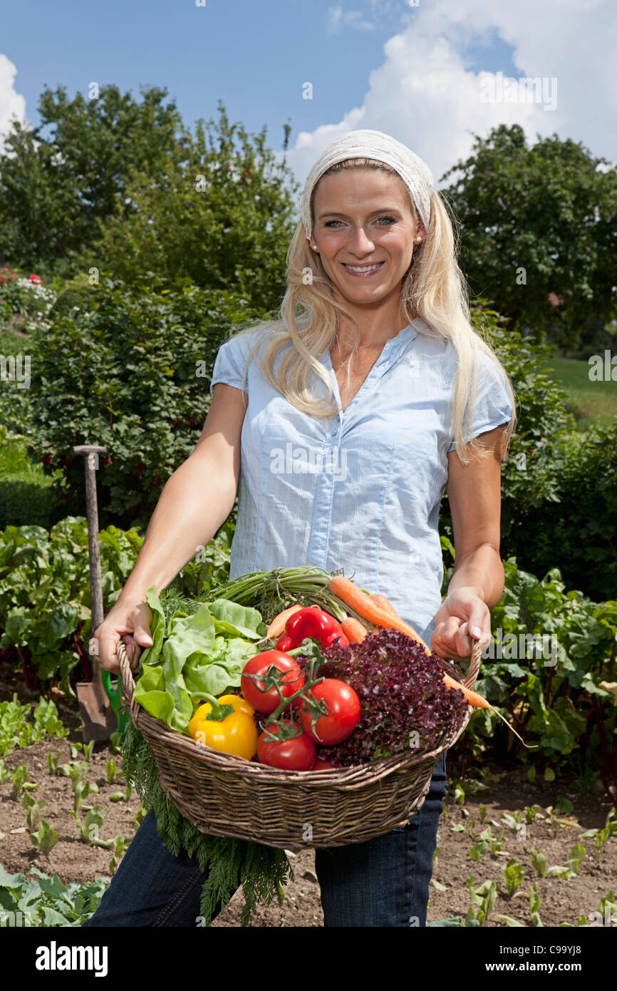 Germany, Bavaria, Altenthann, Woman with basket full of vegetables - Stock Image