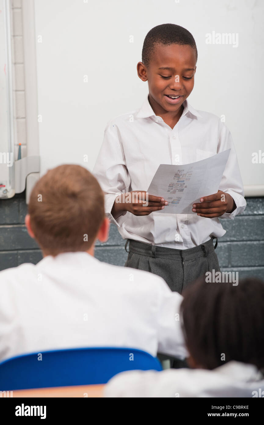 Boy standing in front of class reading in classroom, Johannesburg, Gauteng Province, South Africa - Stock Image