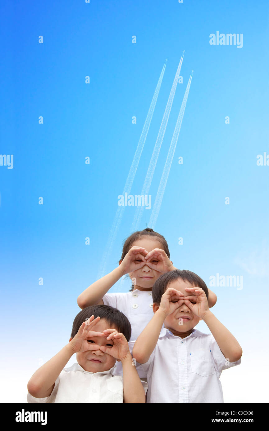 three happy kids watching the aircraft flying through to sky - Stock Image