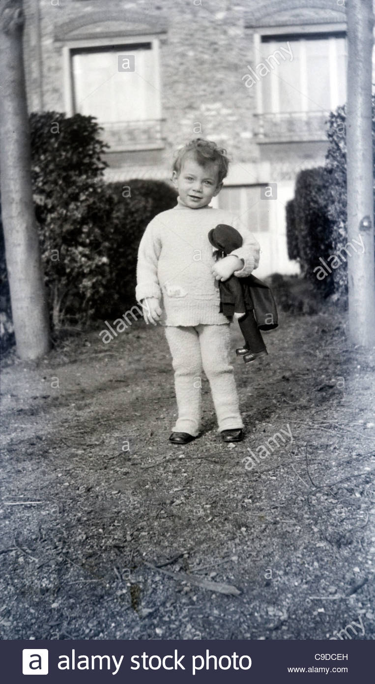 little child holding a doll in the garden 1920s - The Doll In The Garden