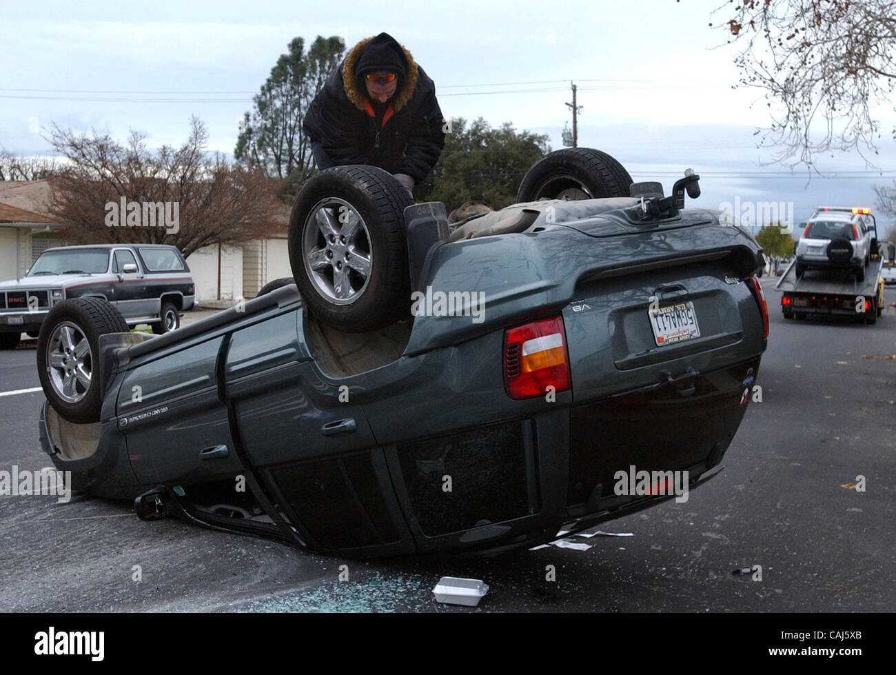 A tow truck operator works on uprighting an overturned 2004 Jeep Grand Cherokee that had been struck by a 1999 Honda - Stock Image