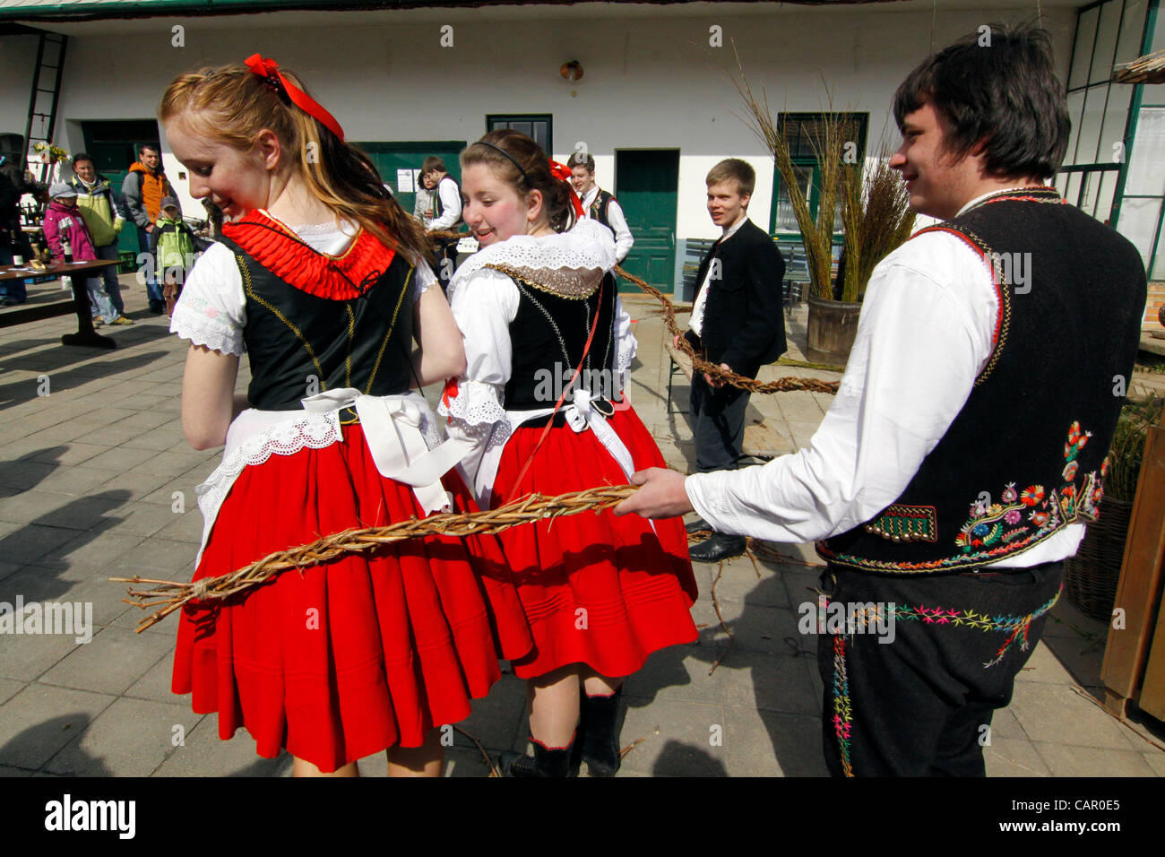 """Boys in folk customs carry a giant """"pomlazka"""" (plated willow stems) to whip girls during traditional celebration Stock Photo"""