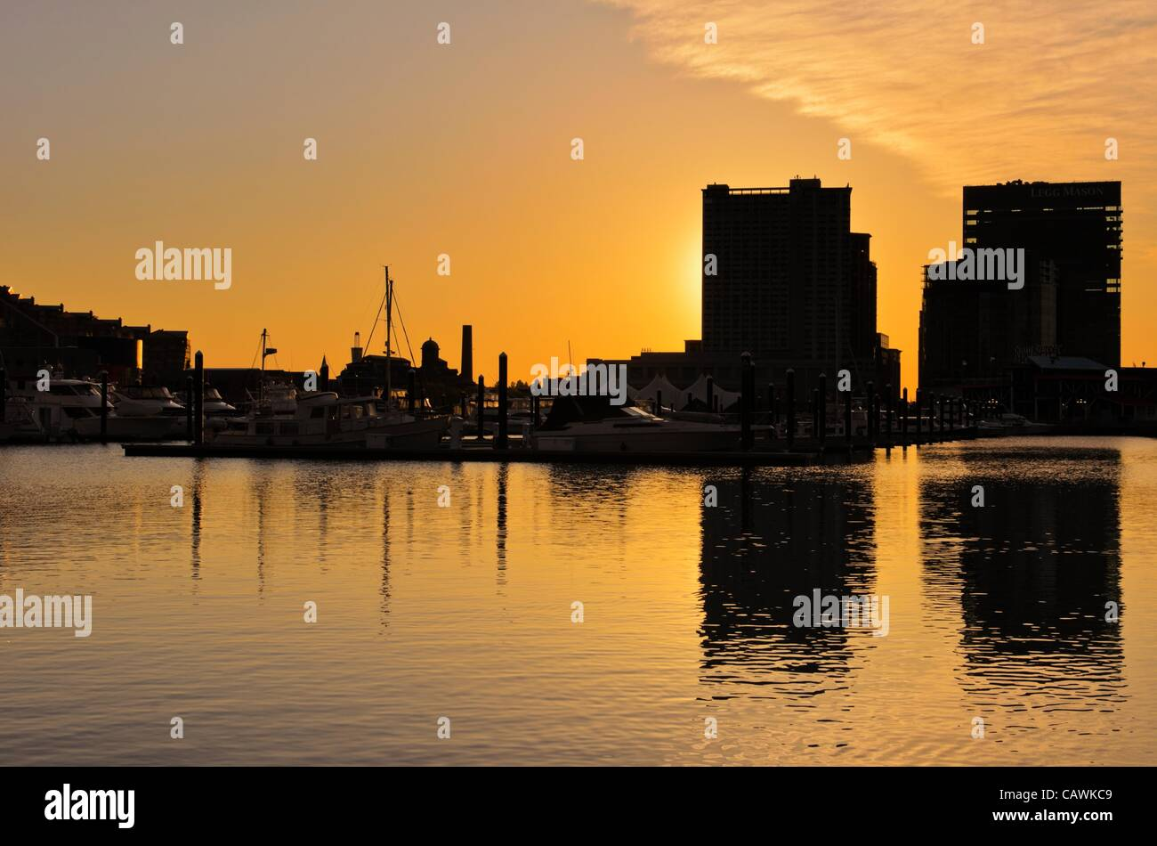 a-dramatic-and-beautiful-sunrise-with-buildings-and-boats-in-silhouette-CAWKC9.jpg