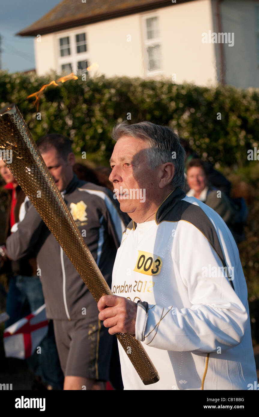 Falmouth, UK. 19 May, 2012. Eric Smith carries the Olympic Torch at Lands End. - Stock Image