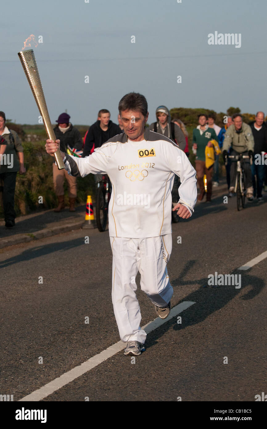 Falmouth, UK. 19 May, 2012. Steve Brady runs with the Olympic Torch at Lands End - Stock Image