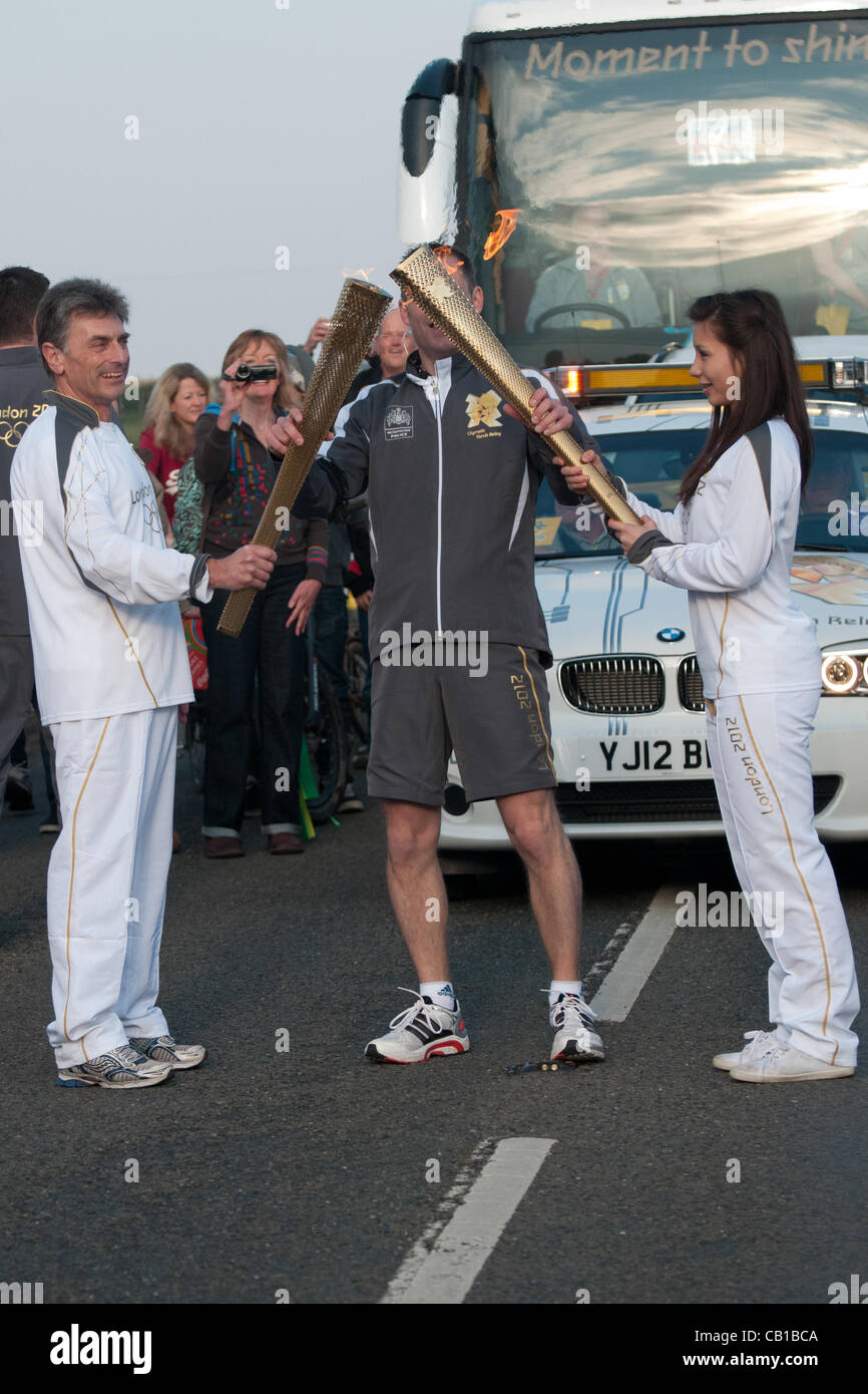 Falmouth, UK. 19 May, 2012. Steve Brady passes the flame from his torch to Vicky Smith at Lands End. - Stock Image