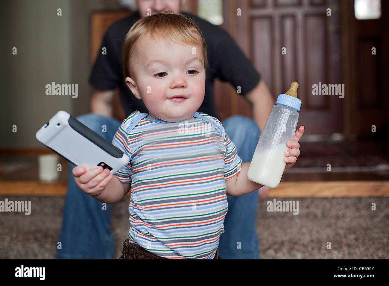 Toddler boy holding has bottle and a smart phone in his hands. - Stock Image