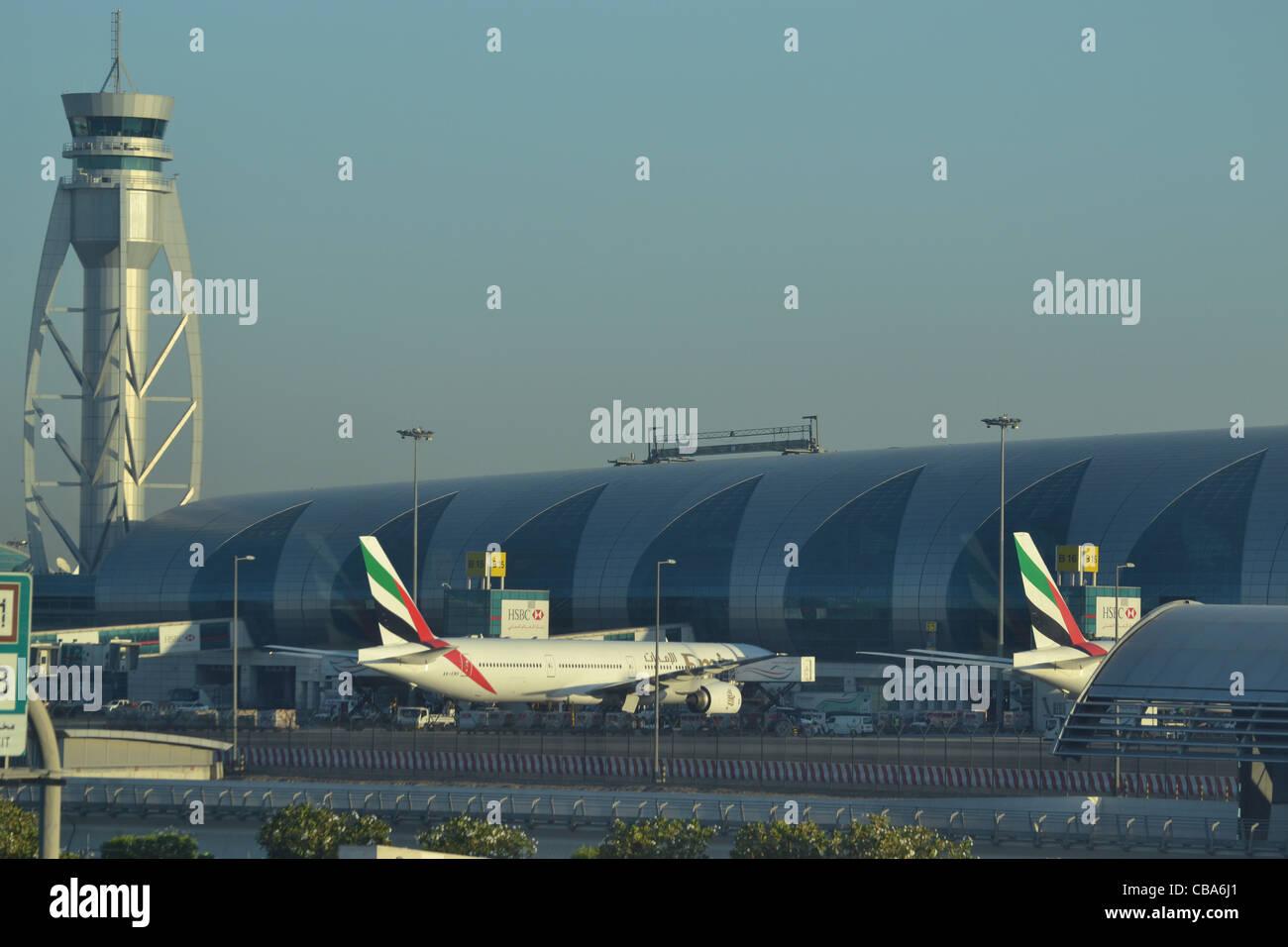 Emirates aircraft and control tower at Dubai Airport, DXB, United Arab Emirates - Stock Image