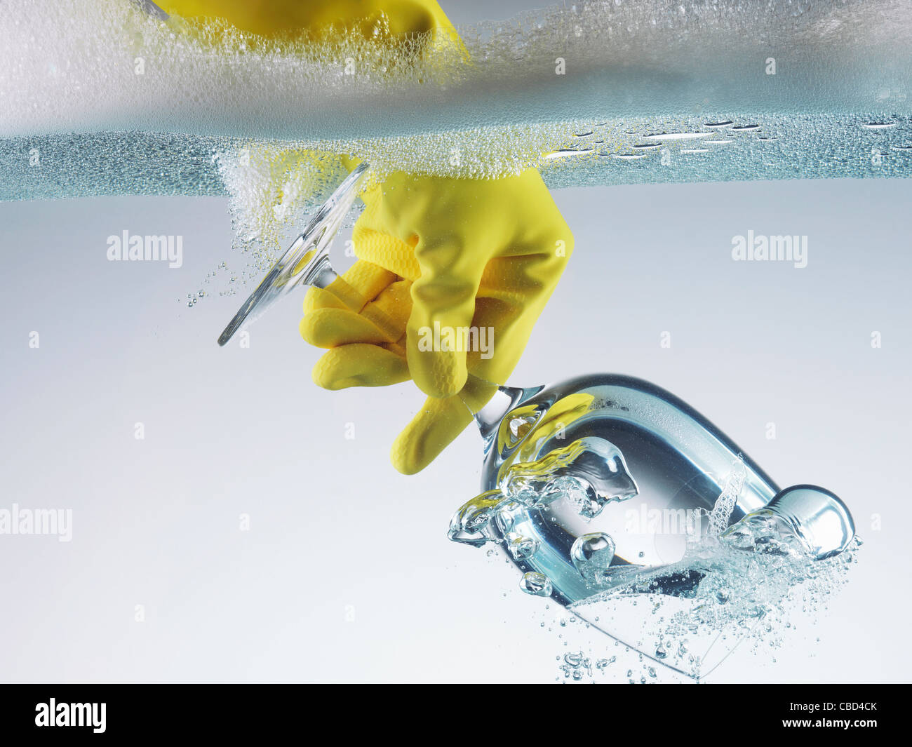 Rubber glove dunking wine glass in water - Stock Image
