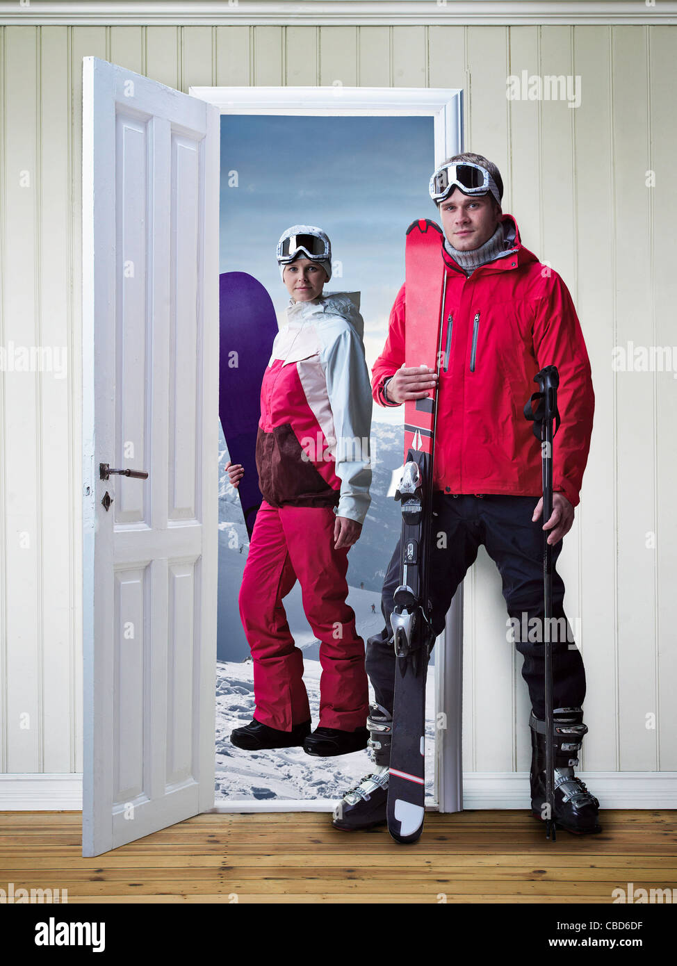 Skiers standing in new house - Stock Image