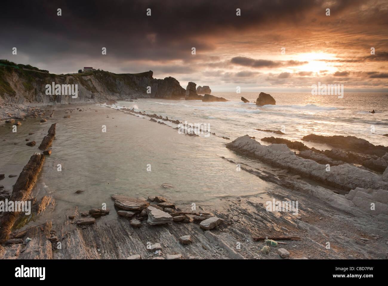 Waves washing up on rocky beach - Stock Image