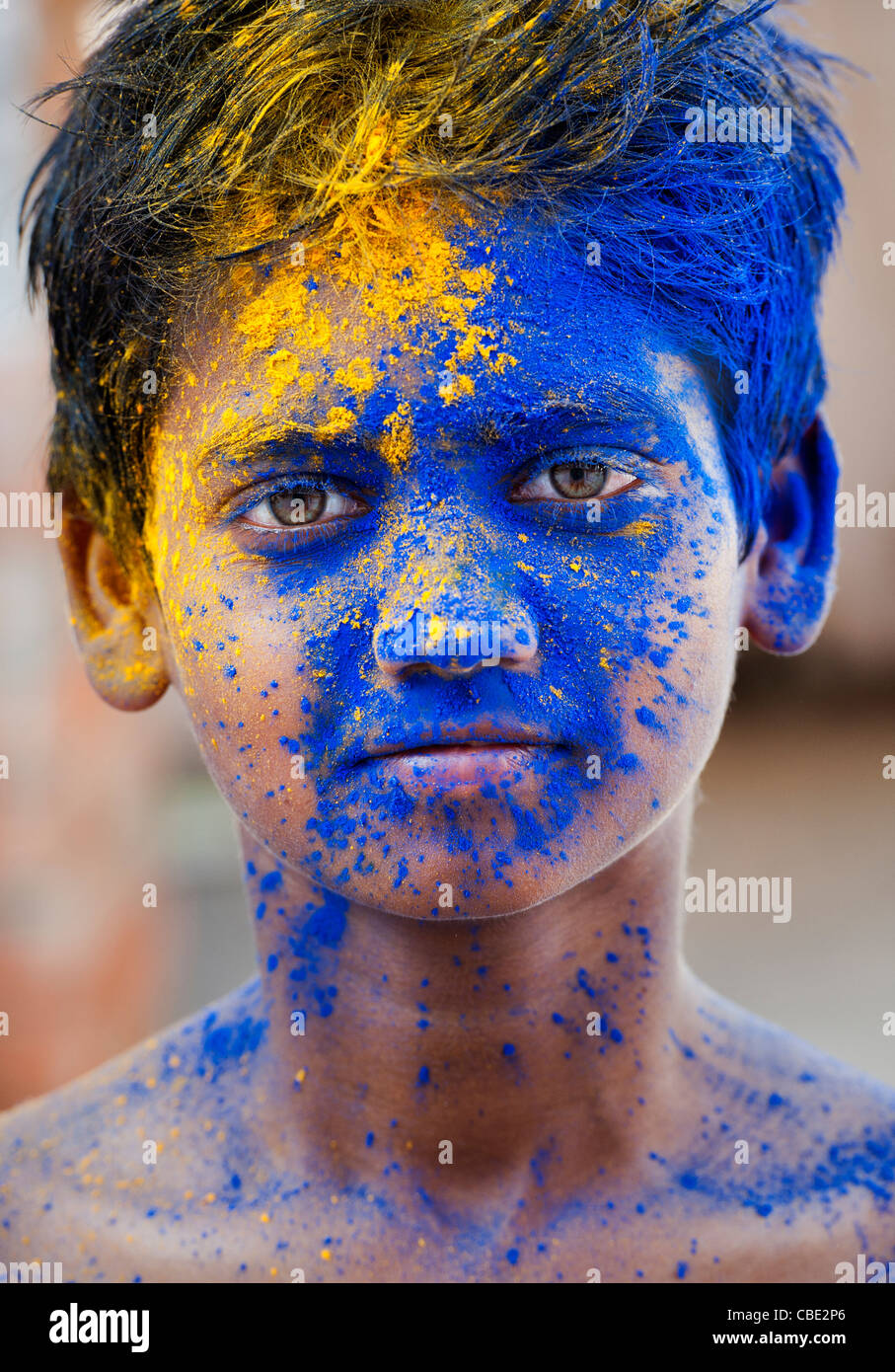 Young Indian boy covered in coloured powder pigment - Stock Image