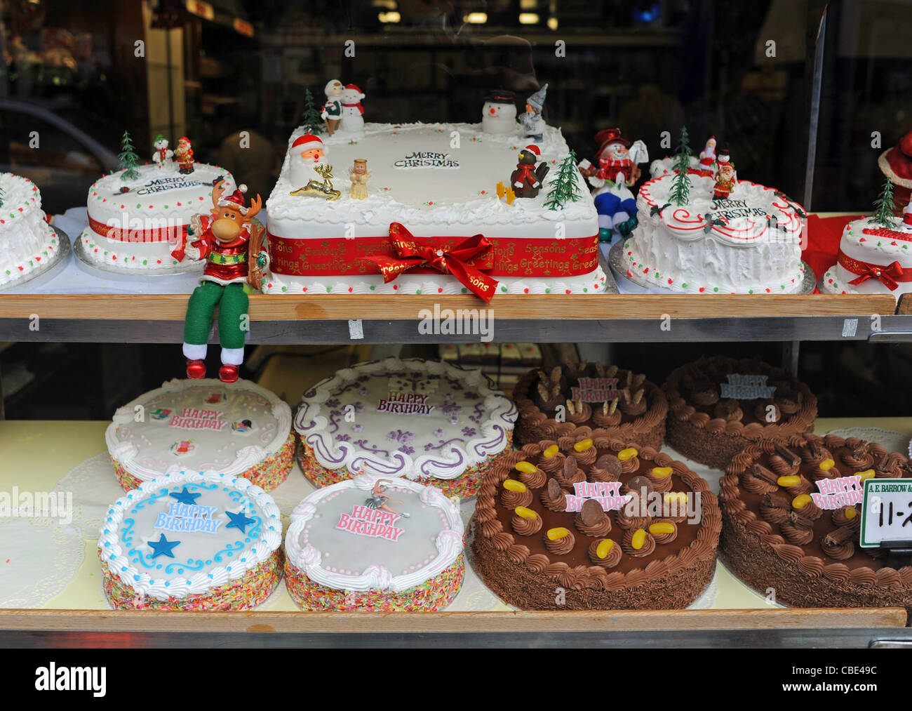Display of Christmas and Birthday cakes in window of shop in Stock