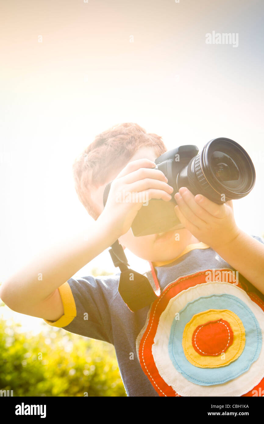 A Young boy, aged 7, using a digital SLR camera in a sunny garden. Stock Photo