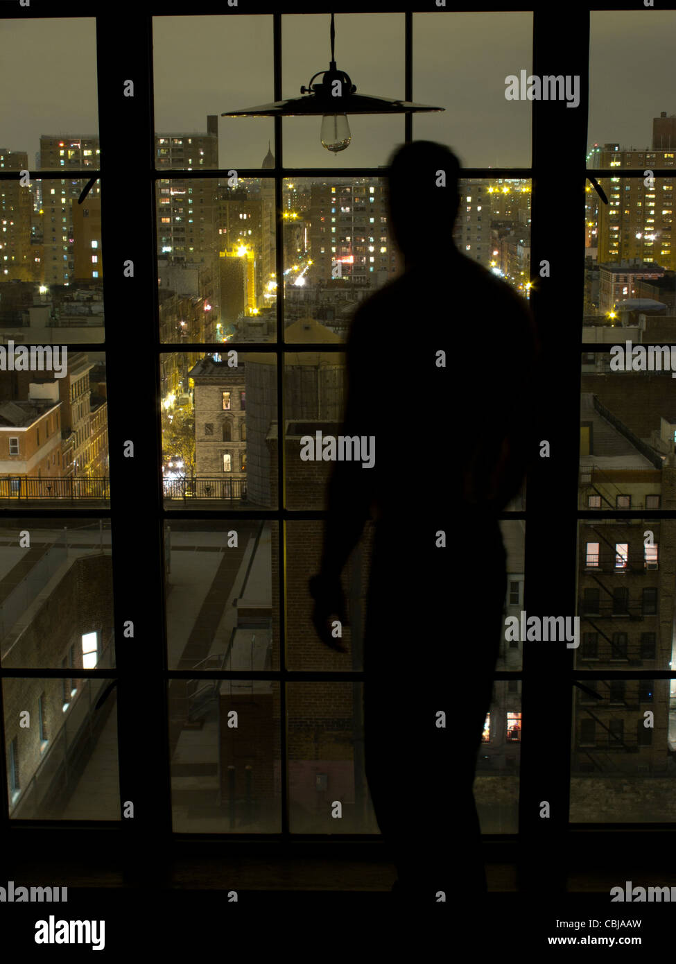 Silhouette of Man at window at night overlooking downtown Manhattan, New York City, New York, USA - Stock Image