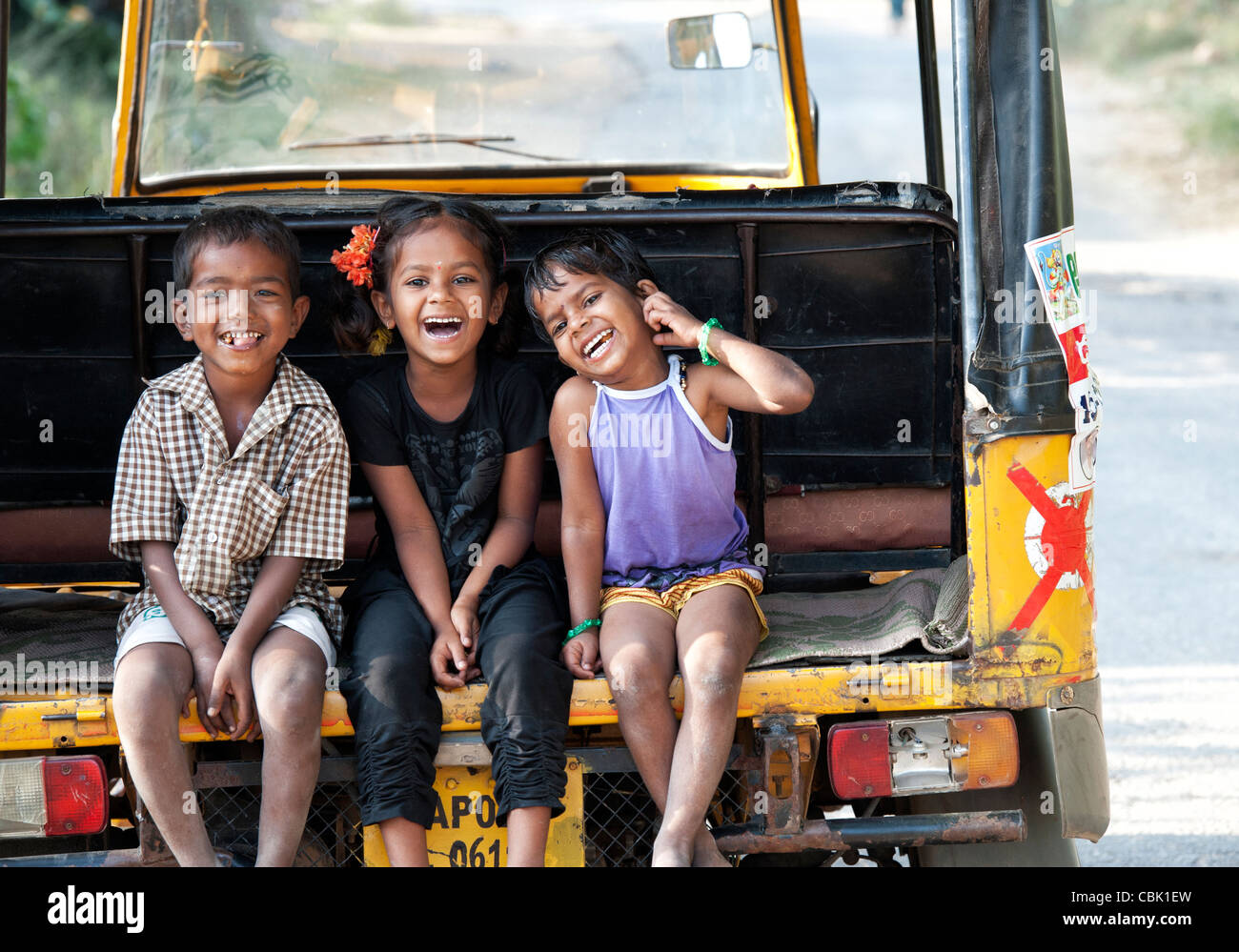 Happy young rural Indian village family children sat in a rickshaw smiling and laughing. Andhra Pradesh, India - Stock Image