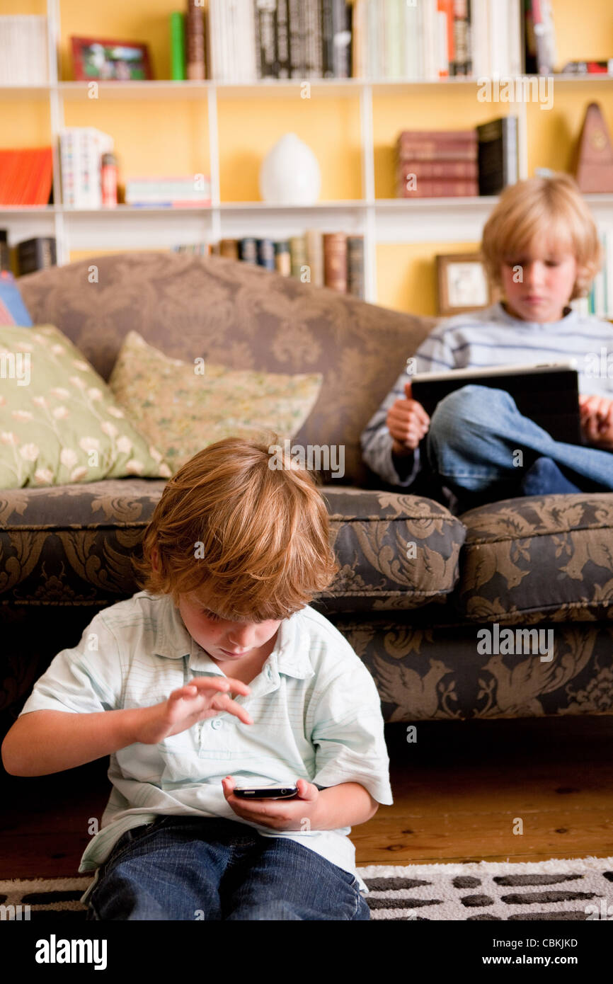 Two boys relaxing at home with a digital tablet and smart phone Stock Photo