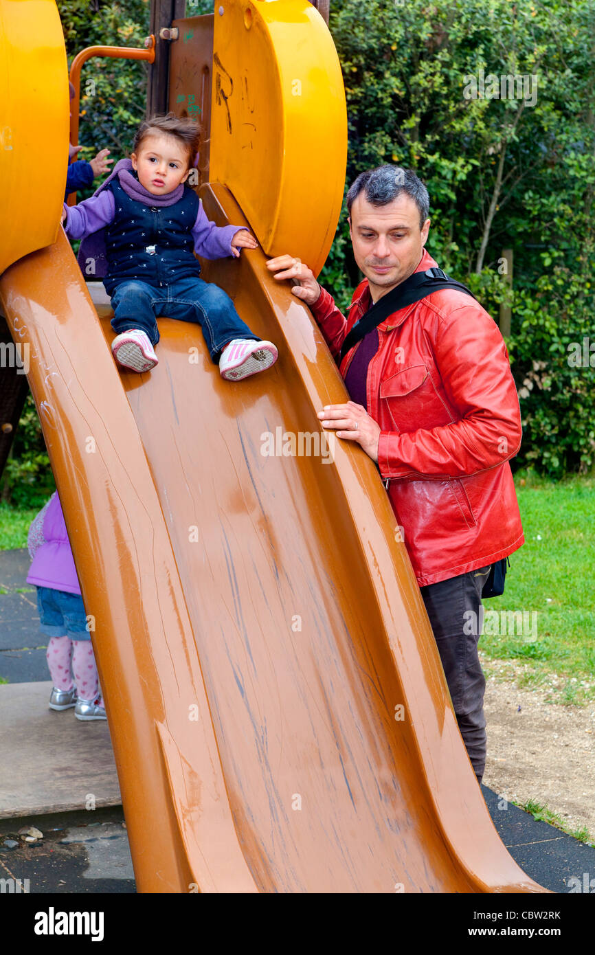 Father and daughter on a playground slide - Stock Image