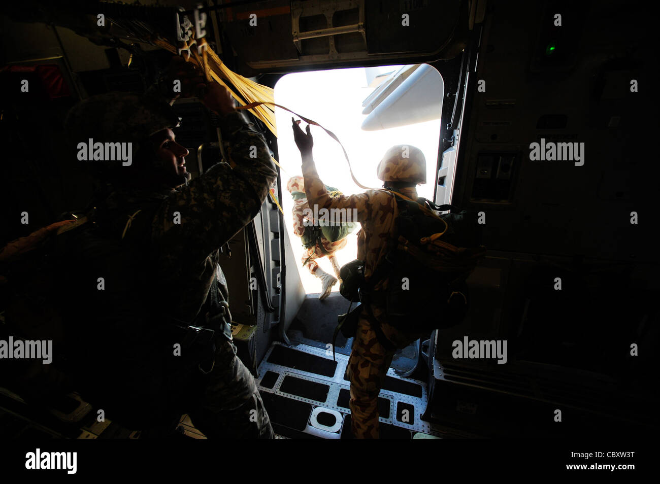 Paratroopers begin their 'friendship jump' from a U.S. Air Force C-17 Globemaster III during Exercise Bright - Stock Image