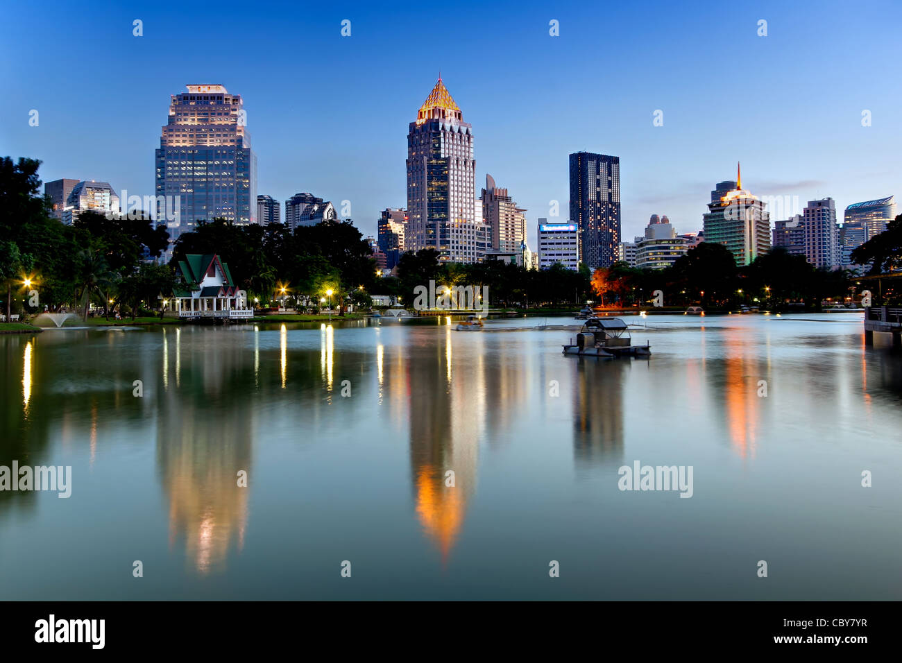 View towards Silom & Rama IV Road from Lumpini Park at Dusk, Bangkok. - Stock Image