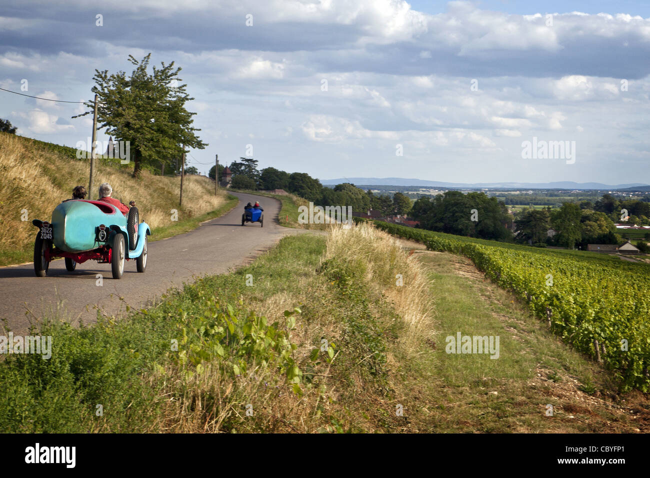 old collectors' cars on route d23 in front of the vineyards of stock