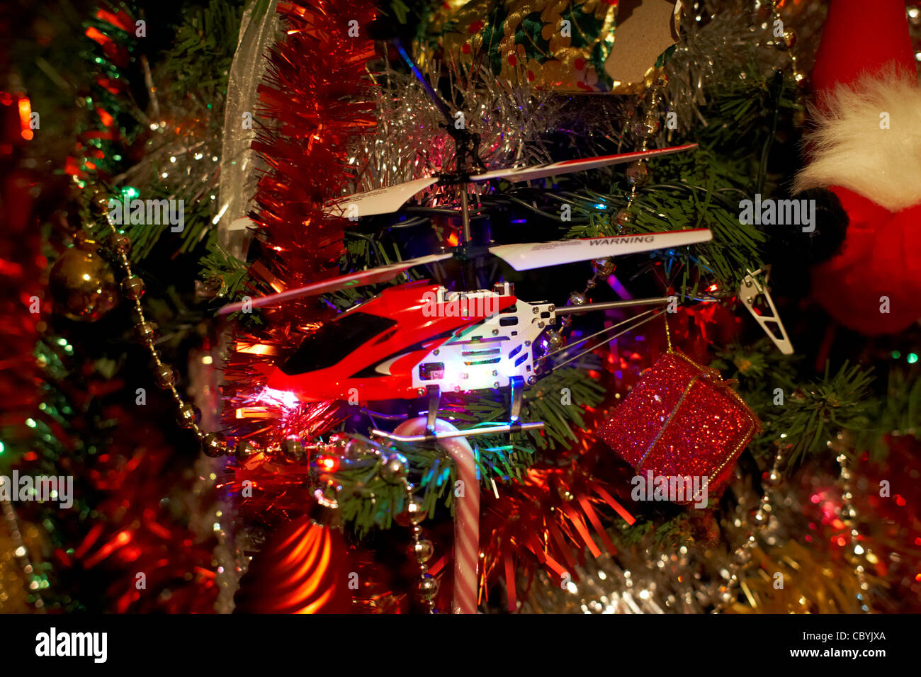 small toy remote controlled helicopter crashed into a christmas tree - Stock Image