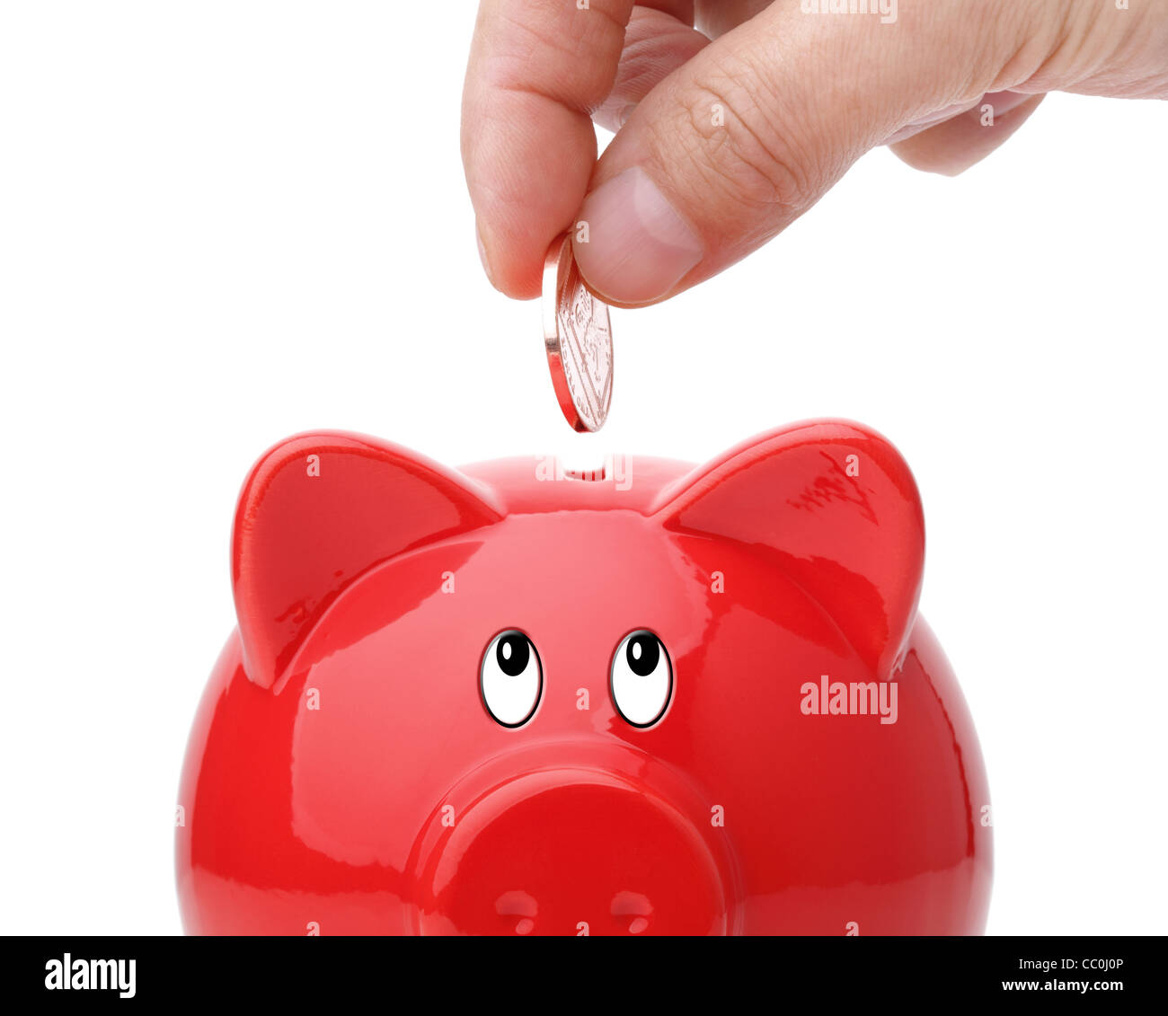Inserting coin into a piggy bank - Stock Image